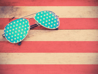 mirror sunglasses on striped red wooden background as American flag pattern
