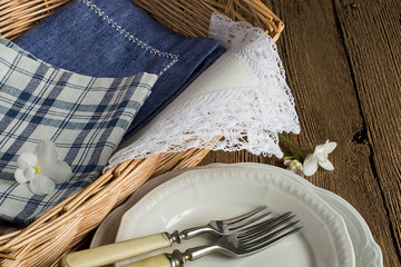 Items for table setting. Canteens napkin in a wicker basket, plates and forks on a brown wooden table.