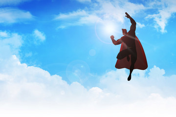 Silhouette of a superhero figure flying on clouds