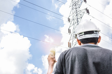 High-voltage tower with blue sky background And electrical engineers Stand holding a light bulb