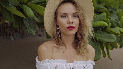 Pretty naturally looking woman in boho style fashion wearing white shirt and hat on a beautiful summer day