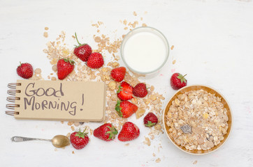 Good morning note in a notebook with craft brown pages, ripe strawberries, milk and oat muesli for breakfast