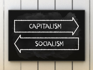 Capitalism or socialism choices on black board written with chalk.