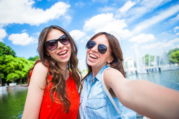 Happy girls making selfie background big fountain. Young tourist friends traveling on holidays outdoors smiling happy.