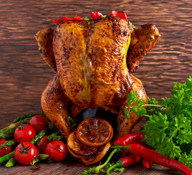 Gourmet Roast Whole organic chicken on cider Can With Asparagus, glazed Cherry Tomatoes, Herb and Spices, Served  Top of a Wooden Table.
