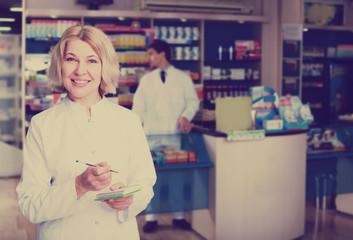 Pharmacist and pharmacy technician posing in drugstore
