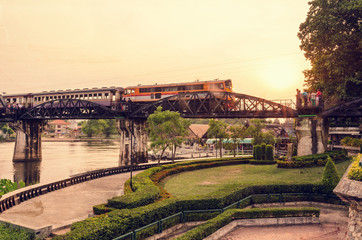 Grunge old photo vintage style trains for travel running on the bridge over the River Kwai is a historical attractions during World War 2 the famous of Kanchanaburi Province in Thailand