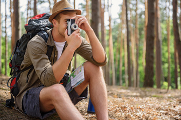 Cheerful male traveler taking photo of forest