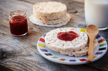 Round rice cakes as breakfast or snack with sweet strawberry jam and a glass of milk.