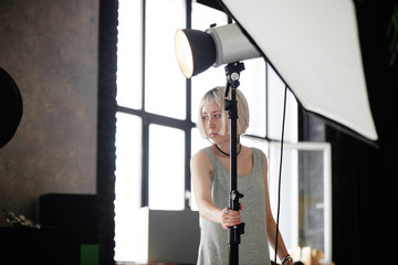 The photographer corrects lighting floodlight in the Studio
