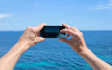 mujer fotografiando el mar