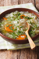 Cabbage soup with vegetables close up in a bowl. vertical