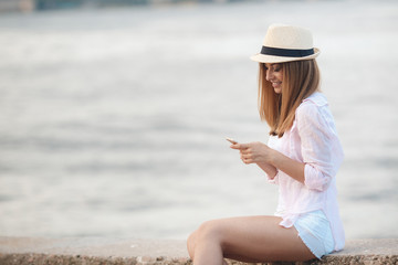 Beautiful woman in beige hat ,a beautiful smile,long blonde straight hair,dressed in a white shirt,sat on the embankment near the blue ocean,reviews the messages to your mobile phone