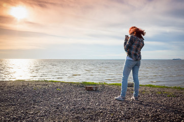 Teenage girl with red hair taking landscape photo