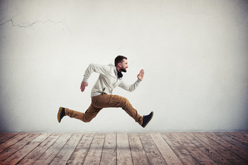 Young bearded man in mid-air running pose over wooden floor