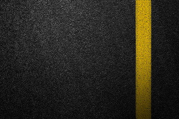 Level asphalted road with a dividing yellow stripes. The texture of the tarmac, top view.