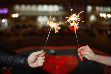 two hands holding fireworks, sparklers, close up