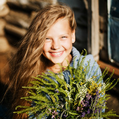 Beautiful girl posing with big bouquet of wild flowers