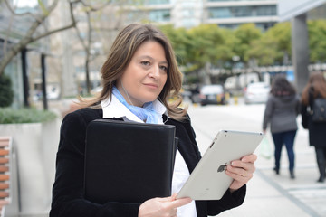 Business woman listening to music with her tablet.