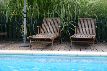 Two wooden sun loungers by the side of a swimming pool