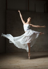 Beautiful ballet dancer in white costume with waving skirt dancing