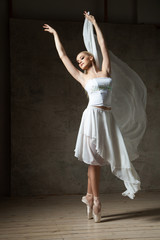 Elegant ballerina dancing in white costume and ballet shoes