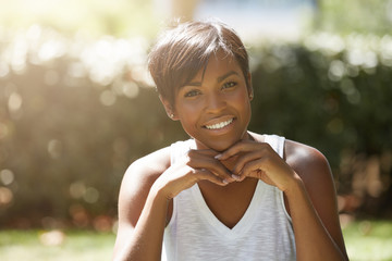 Cropped portrait of stylish charismatic dark-skinned female dressed casually posing with happy smile and hands on her chin, sitting on the green lawn against blurred background of green nature