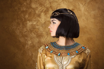 Beautiful woman like Egyptian Queen Cleopatra on golden background. Side view, face profile