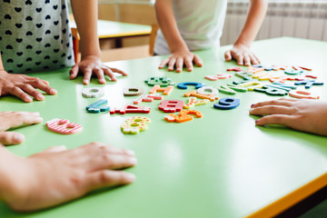 Child hands with wooden toy plate alphabet