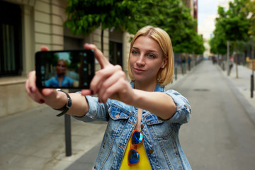 Gorgeous young woman making self portrait with mobile phone camera