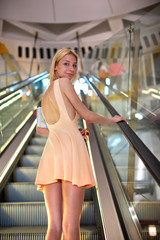 Attractive young woman dressed in bright color dress is standing on escalator in shopping center