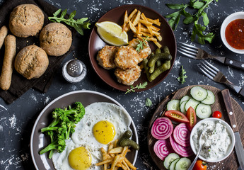 Lunch table - fried eggs, fish balls, potato chips, vegetables, sauces, homemade bread on a dark background. Rustic style, top view