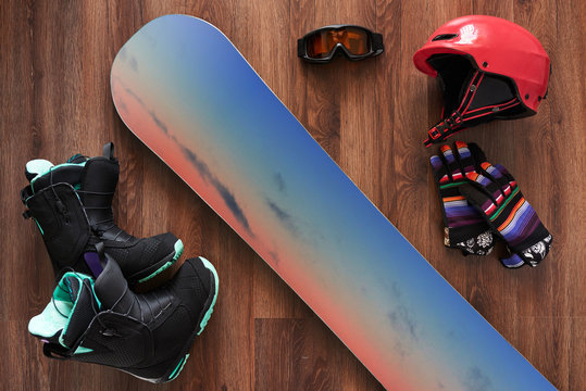 set of snowboard boots, helmet, gloves and mask on wooden