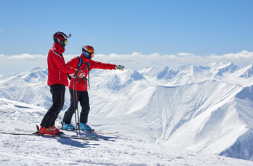 Two skiers are on edge of a cliff in mountains