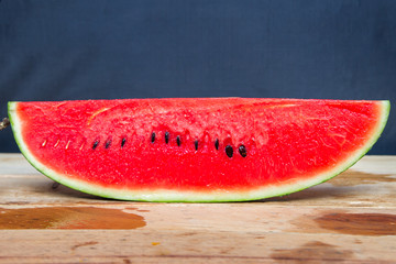 Slices of watermelon on a coconut on the wooden table.