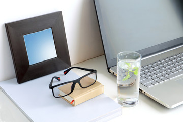 Working calm. Water glass with a mint leaf in work space - nearby the book (magazine) and laptop (computer notebook), framed picture or mirror on white.