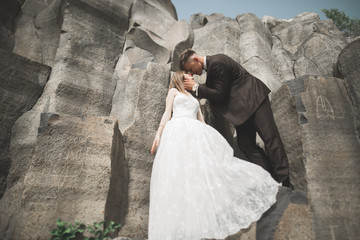 Wedding couple posing on great stones. The bride and groom