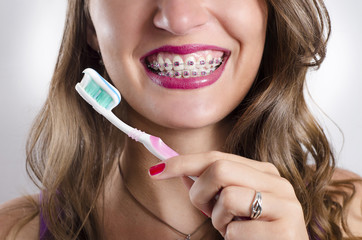 Young woman with perfect teeth and braces holding toothbrush and toothpaste
