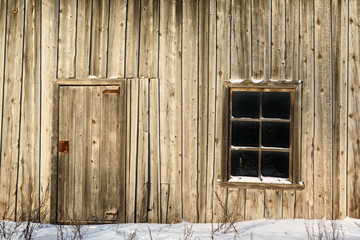 Door and window on wall of an old wooden barn
