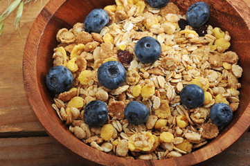 healthy Breakfast - cereal with blueberries in a wooden bowl