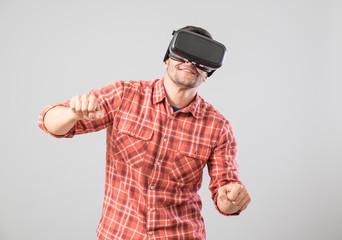 Man with virtual reality glasses paying bike simulator