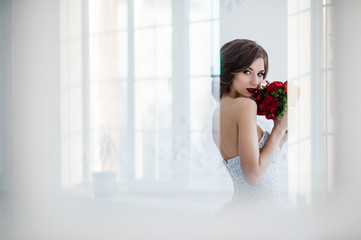 Glamorous young bride with flowers wearing wedding dress standing in front of doors indoors at luxury interior room