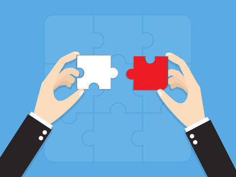 hands of businessman putting wrong way jigsaw puzzle pieces