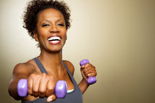 Happy African American fitness woman lifting dumbbells smiling and energetic.