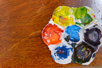 art palette with paint on wooden plank