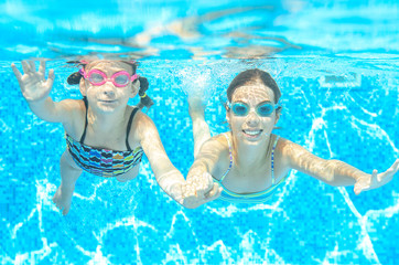Children swim in pool under water, happy active girls in goggles have fun, kids sport on active family vacation