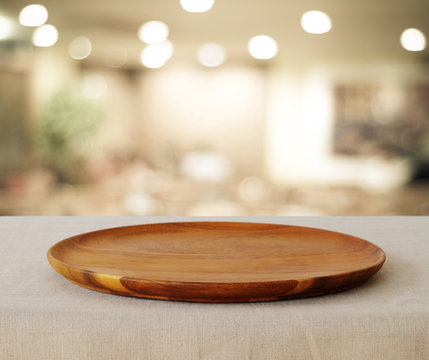 Empty wooden round tray over blurred cafe background