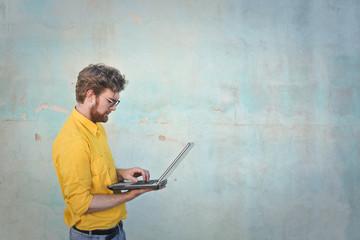 Man in yellow shirt using a laptop
