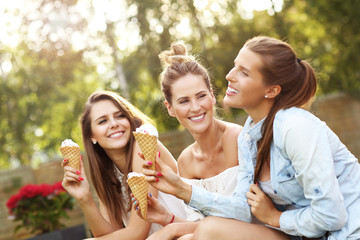 Happy group of friends eating ice-cream outdoors