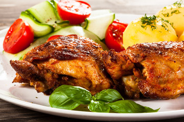 Barbecued chicken legs with boiled potatoes and vegetables